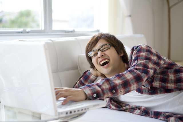 パソコンを部屋で楽しんでいる男性