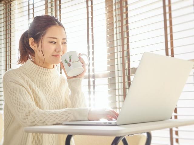 紅茶を飲みながらパソコンを見ている女性