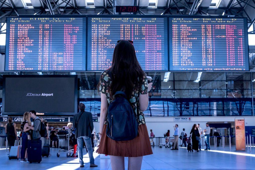 空港で電光掲示板を確認する女性